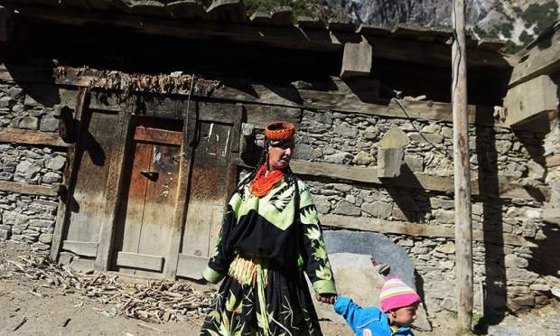 In this photograph taken on October 31, 2015, a Kalash woman walks with a child past a Kalash house of worship in the Brun village of Bumboret valley. — AFP