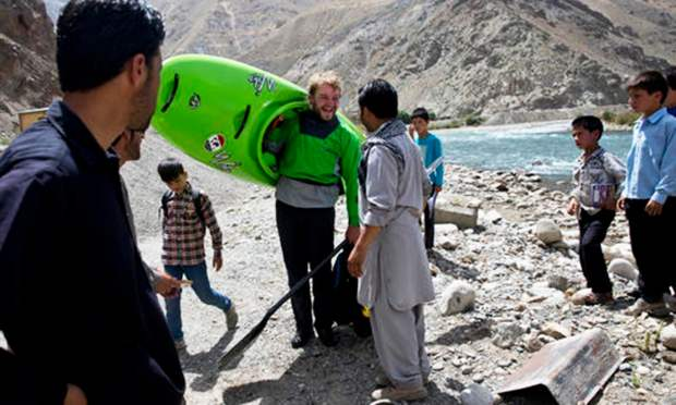 Scottish tourist Callum Strong, in green, chats with his Afghan guide after kayaking along the Panjshir River in Panjshir province, north of capital Kabul, Afghanistan.—AP