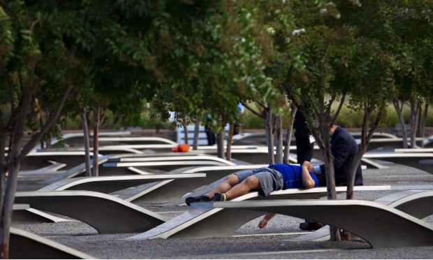 Family members sit on a memorial bench before the observance ceremony to mark the15th anniversary of the 9/11 attacks at the Pentagon Memorial in Washington DC.  — AFP