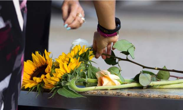 Family member splace flowers on a memorial bench before the observance ceremony to mark the15th anniversary of the 9/11  attacks at the Pentagon Memorial in Washington, DC. — AFP