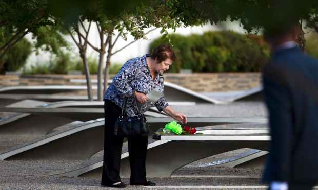 Family member places flowers on a memorial bench before the observance ceremony to mark the15th anniversary of the 9/11 terrorist at the Pentagon Memorial in Washington DC. — AFP