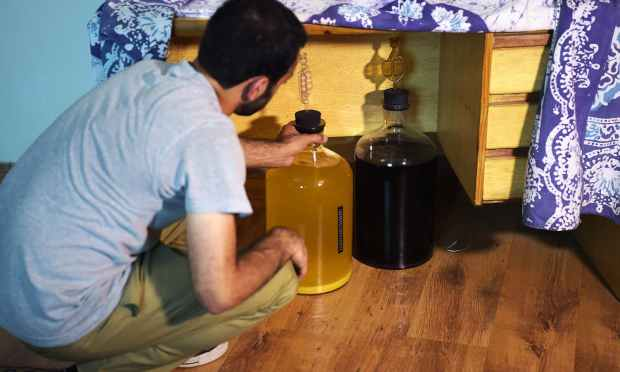 In this photograph taken on June 29, 2016, a resident places bottles of homemade whisky under a table at his home in Islamabad. ─ AFP