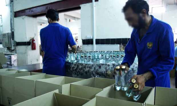 In this photograph taken on June 28, 2016, workers pack bottles of whisky at the Muree Brewery Company in Rawalpindi. ─ AFP