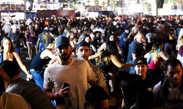 People flee the Route 91 Harvest country music festival grounds after an active shooter was reported. ─ AFP