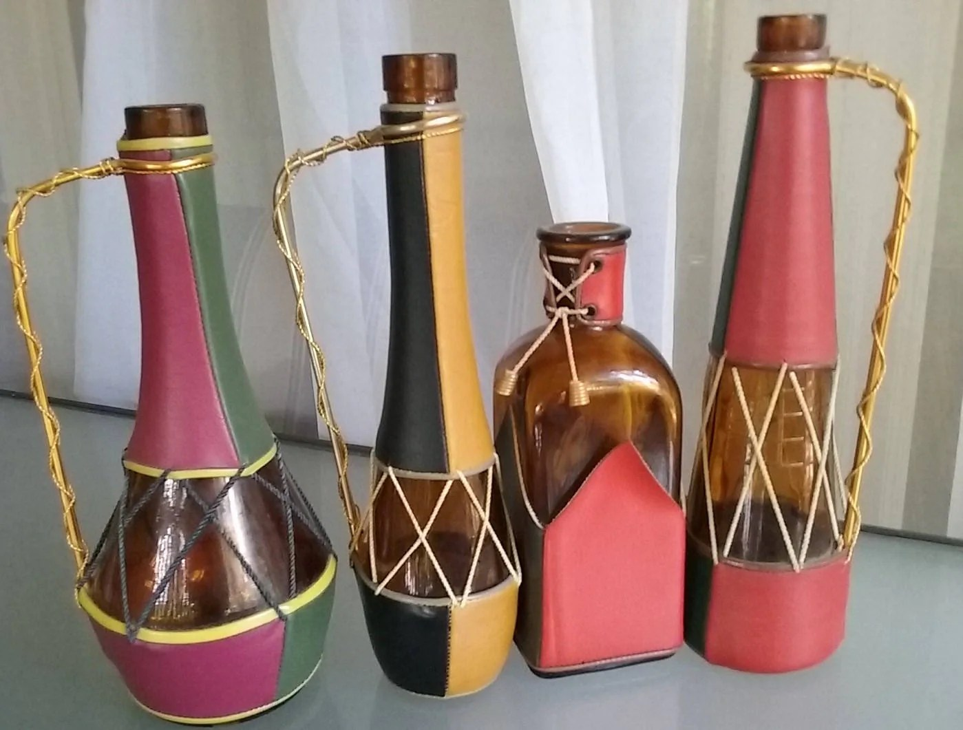 Interesting Bottles Leather Covered Decanters Set Of Four Bottles Vintage Bottles Decanters Amber Glass Metal Handles Multi Colored Leather Spain