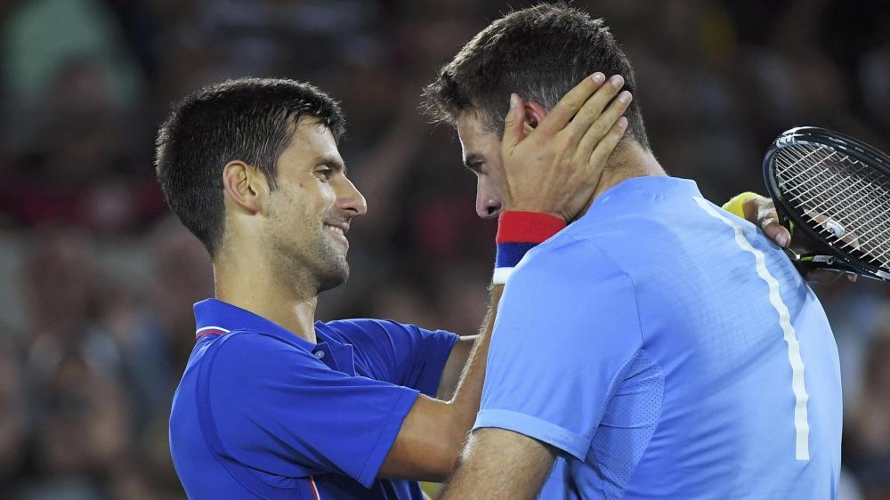Novak Djokovic embraces Juan Martin del Potro after losing his opening game in the Rio Olympics