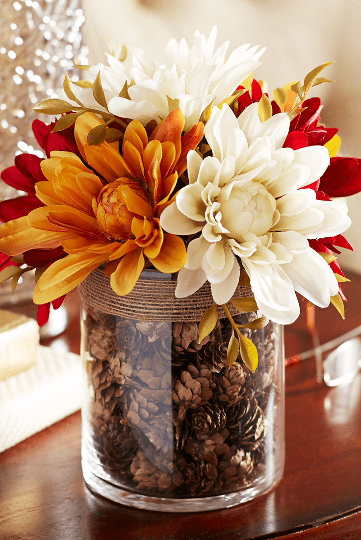 Faux dahlias in a vase filled with pinecones makes perfect tabletop focal point