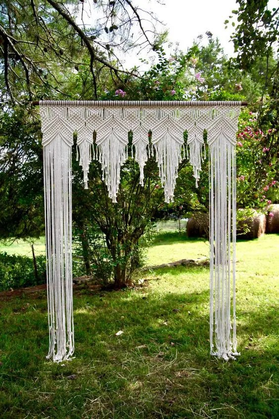 macrame covered wedding arch looks boho and gypsy at the same time