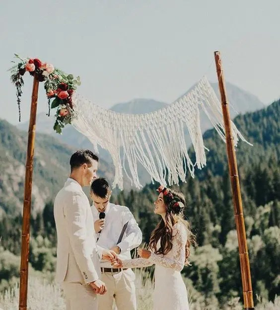 bamboo wedding arch with a macrame hanging and bold flower accents