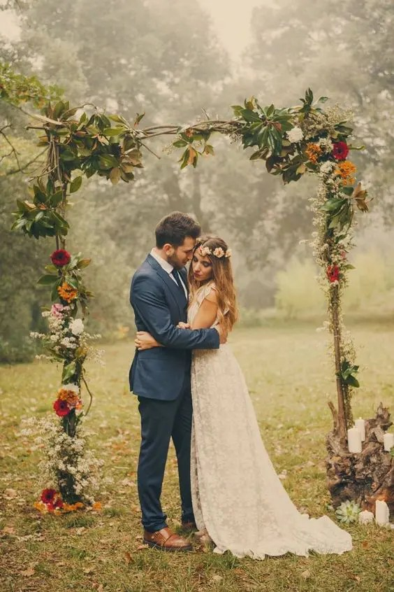 branch wedding arch with leaves and bold flowers for a fall wedding