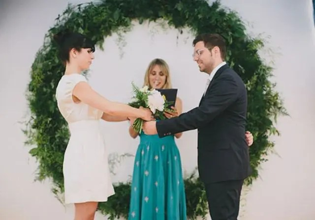 a giant greenery wreath as a backdrop for a modern urban ceremony