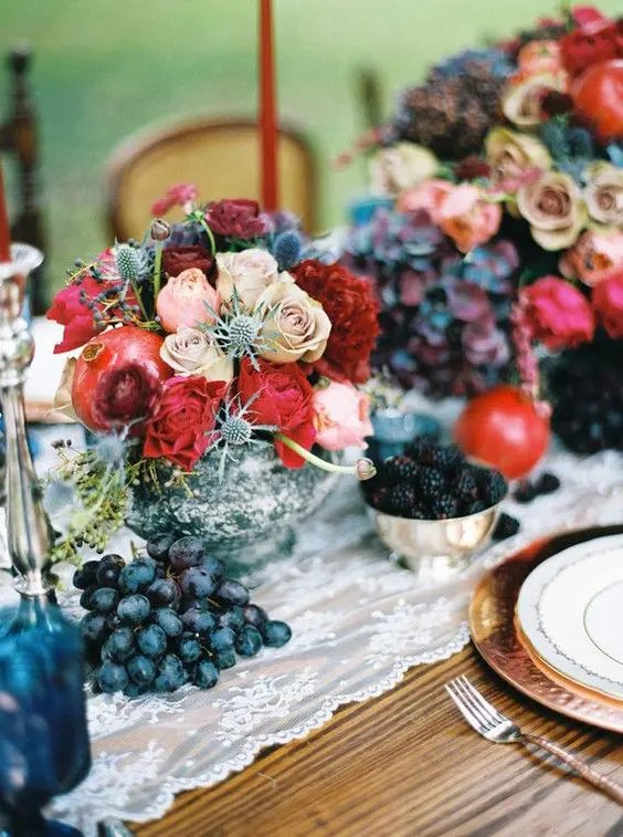 a lush centerpiece with dusty pink roses, thistles, pomegranates and red blooms for a colorful winter celebration