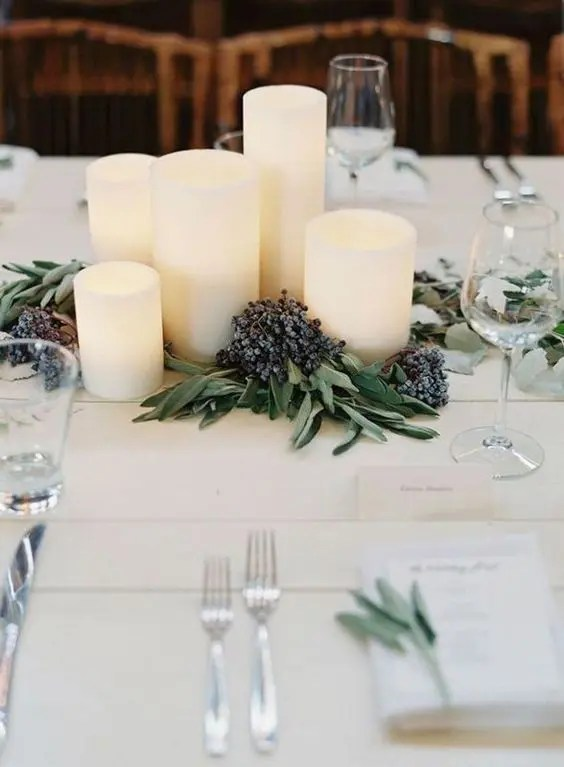 pillar candles placed on the table with privet berries look very wintery-like