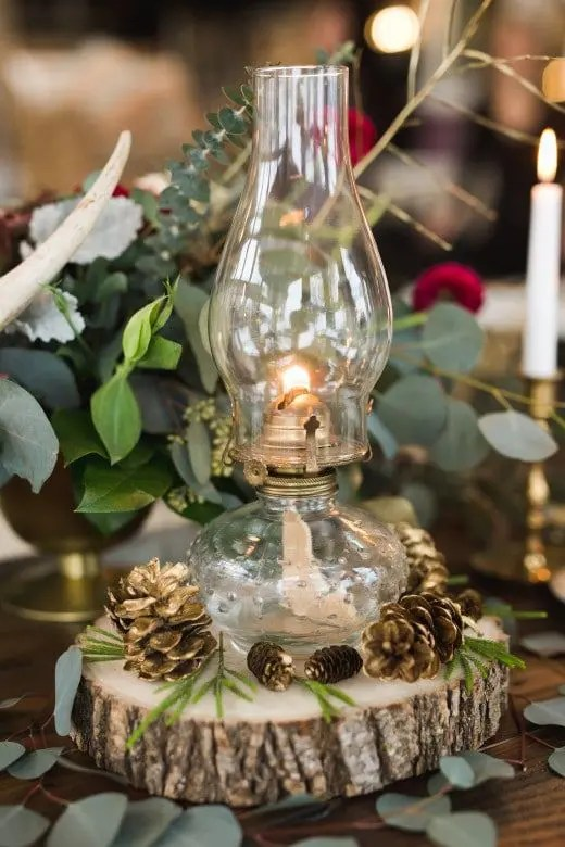a Betty lamp placed on a wooden slice with gilded pinecones looks chic and simple
