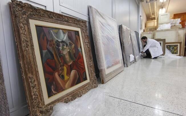 Funcionário manuseia obras de artistas brasileiros apreendidas pela PF na Operação Lava Jato, em 16 de maio