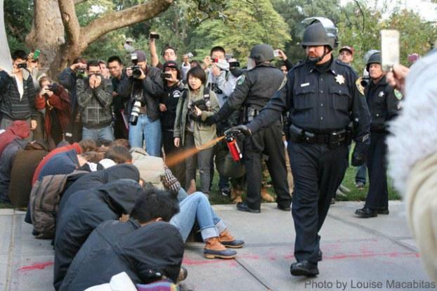 Policjant atakuje gazem kulących się ludzi
