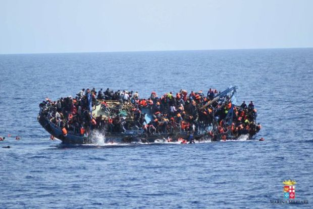 "Migrants are seen on a capsizing boat before a rescue operation by Italian navy ships ""Bettica"" and ""Bergamini"" (unseen) off the coast of Libya in this handout picture released by the Italian Marina Militare on May 25, 2016."