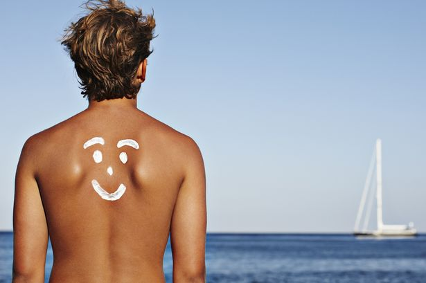 Man with a suncream smiley face