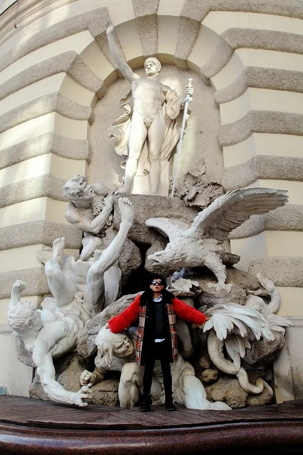 Bryanboy in front of Die Macht zu Lande (The Power on Land) fountain by Edmund Hellmer at Michaelertrakt of Hofburg Palace