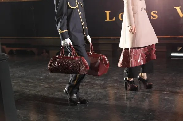 Two Louis Vuitton bags carried by a Porter