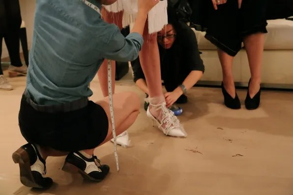 Jessica Stam trying on shoes for Marchesa spring/summer 2013 fashion show