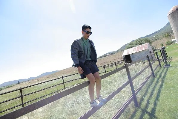 Bryanboy standing on a farm fence in Utah