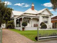 Timber edwardian house exterior with balcony & landscaped ...