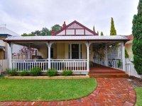 Brick victorian house exterior with verandah & landscaped ...