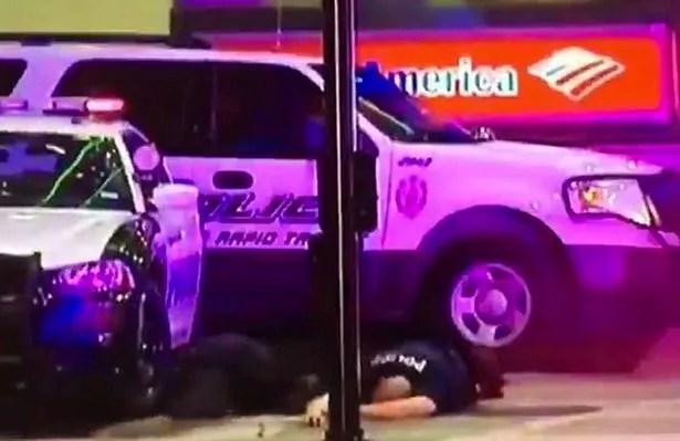 A police officer lies stricken next to cop cars