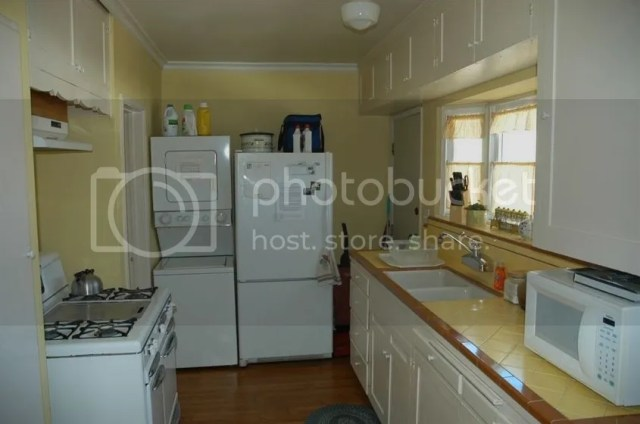 yellow vintage kitchen with original tile counter top and white cabinets