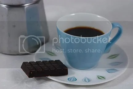 photo of espresso maker, pottery cup and chocolate bar