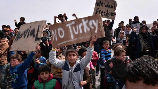 A migrant boy holds up a sign reading 'No Turkey'