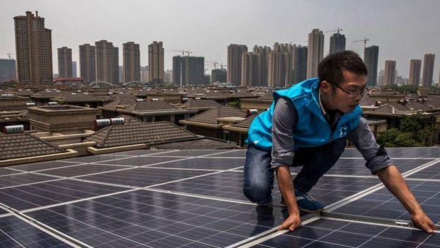 Hombre colocando paneles solares en China.