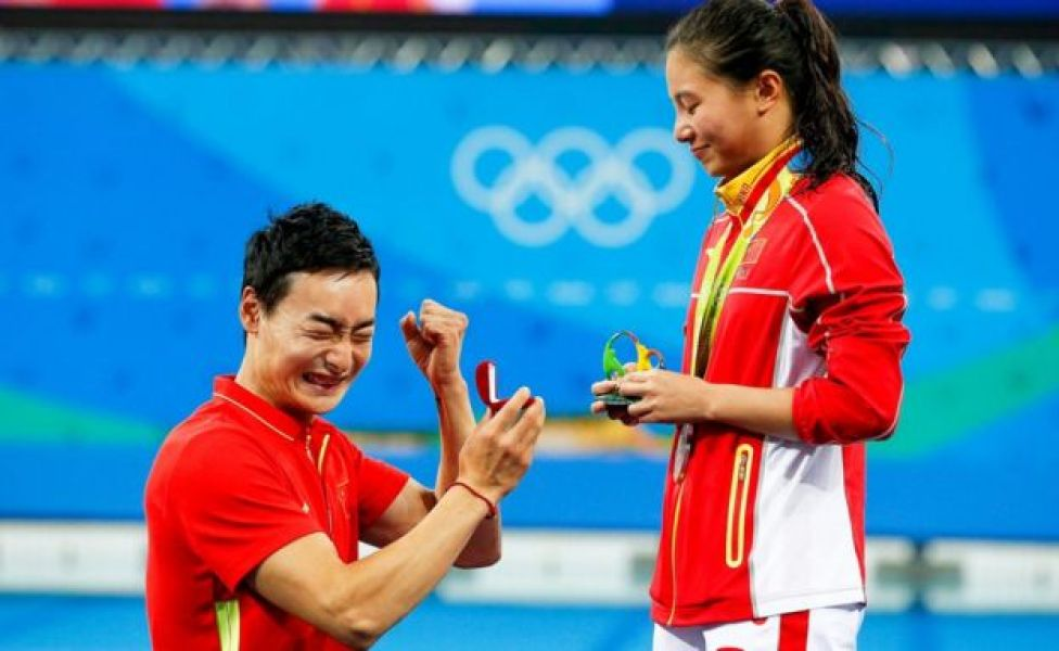 He Zi (R) of China receives a marriage proposal from Chinese diver Ki Qin (L) after winning the silver medal in the women