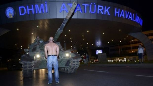 A man stands in front of a Turkish army tank at Istanbul's Ataturk airport. Photo: 16 July 2016