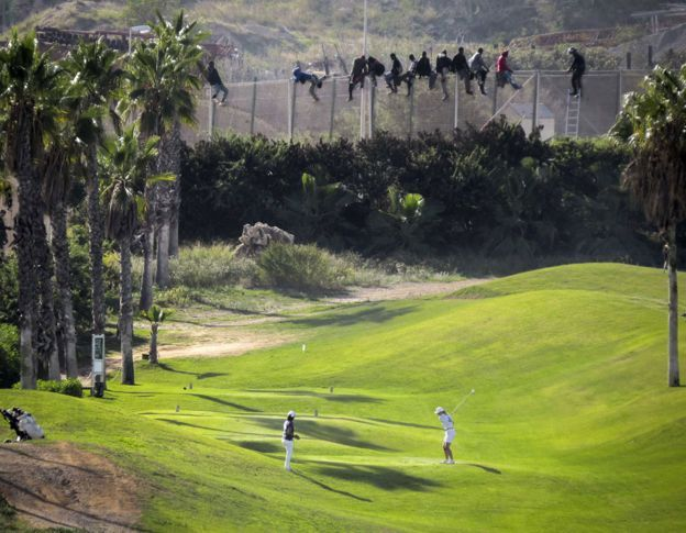 Inmigrantes permanecen sobre la valla de Melilla, junto a un campo de golf