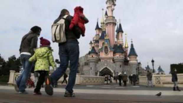 A family outside the Sleeping Beauty Castle at Disneyland Paris