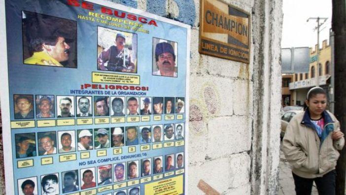 Mujer camina frente a un afiche con las fotos de los miembros del Cartel de Sinaloa, 2005