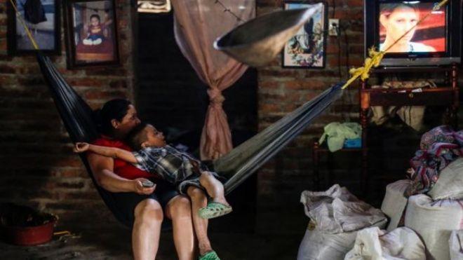 Una mujer y un niño miran televisión en Nicaragua