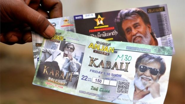 A fan shows movie tickets for Indian actor Rajinikant