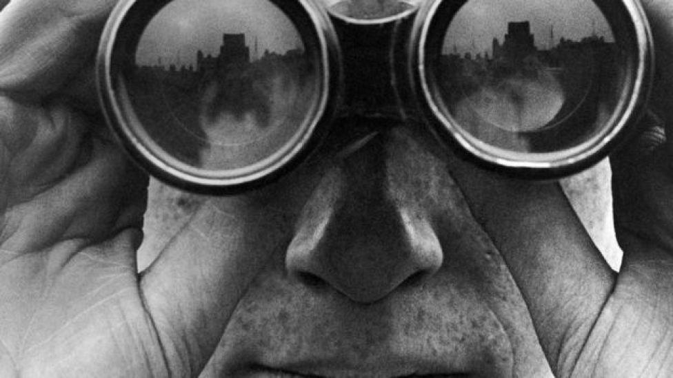 Un plano muy cercano de una persona mirando por unos binoculares, en una fotografía en blanco y negro