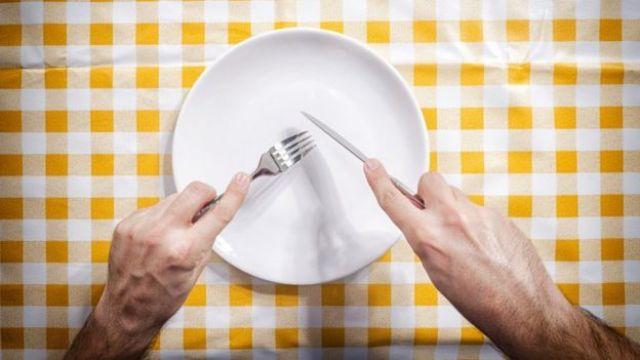 Tenedor y cuchillo a punto de raspar un plato.