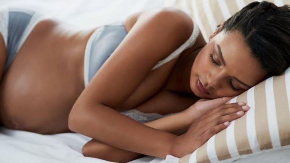 Mujer embarazada durmiendo.