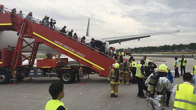 пассажиры спускаются по трапу с самолета в аэропорту Сингапура