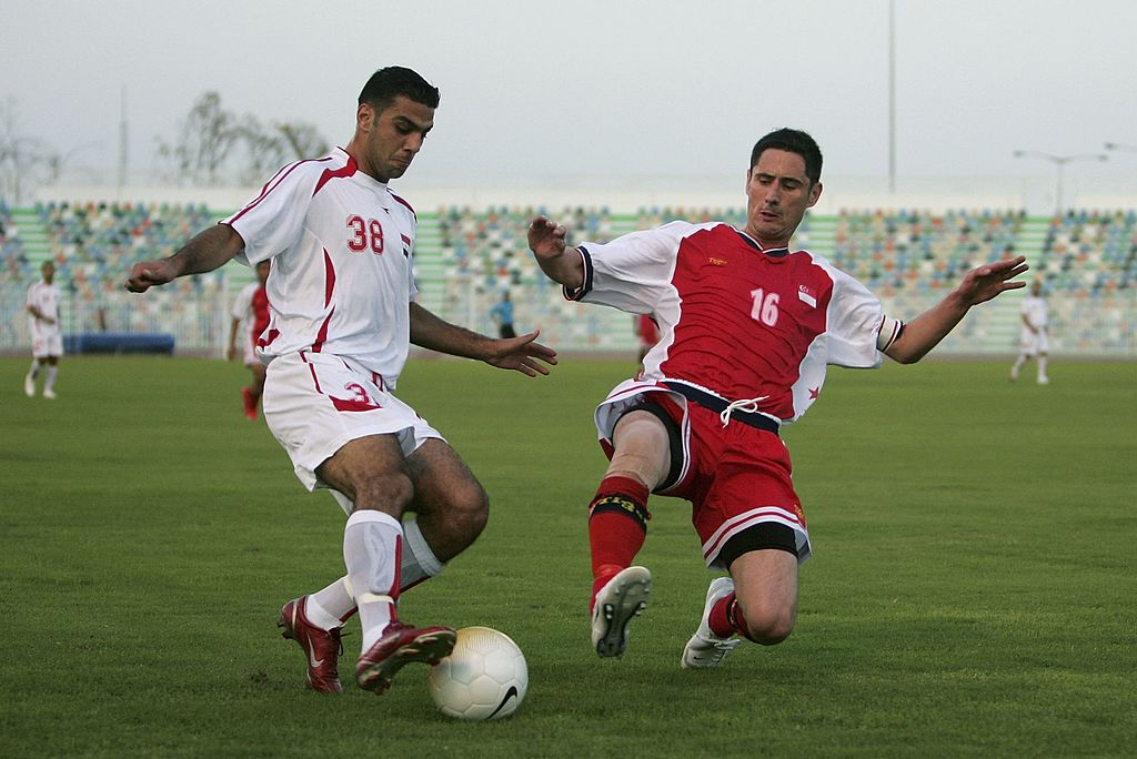 DOHA, QATAR - NOVEMBER 18: Bakri Tarab of Syria is challenged by Daniel Mark Bennett of Singapore during the 15th Asian Games Doha 2006 Men's Group B 1st Round Football match between Singapore and Syria at Al-Ahli Sports Club on November 18, 2006 in Doha, Qatar. (Photo by Julian Finney/Getty Images for DAGOC)