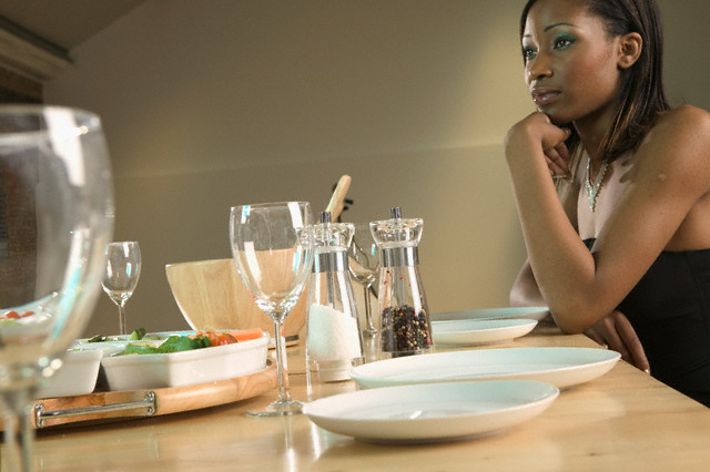Young woman thinking at dining table --- Image by © Neil Guegan/Corbis