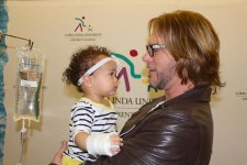 courtesy photo/lluch  The Voice winner, Craig Wayne Boyd, holds young fan Sanai Garcia, a patient at LLUCH.
