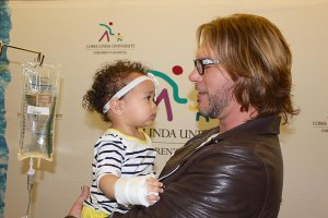 courtesy photo/lluch</p> <p>The Voice winner, Craig Wayne Boyd, holds young fan Sanai Garcia, a patient at LLUCH.