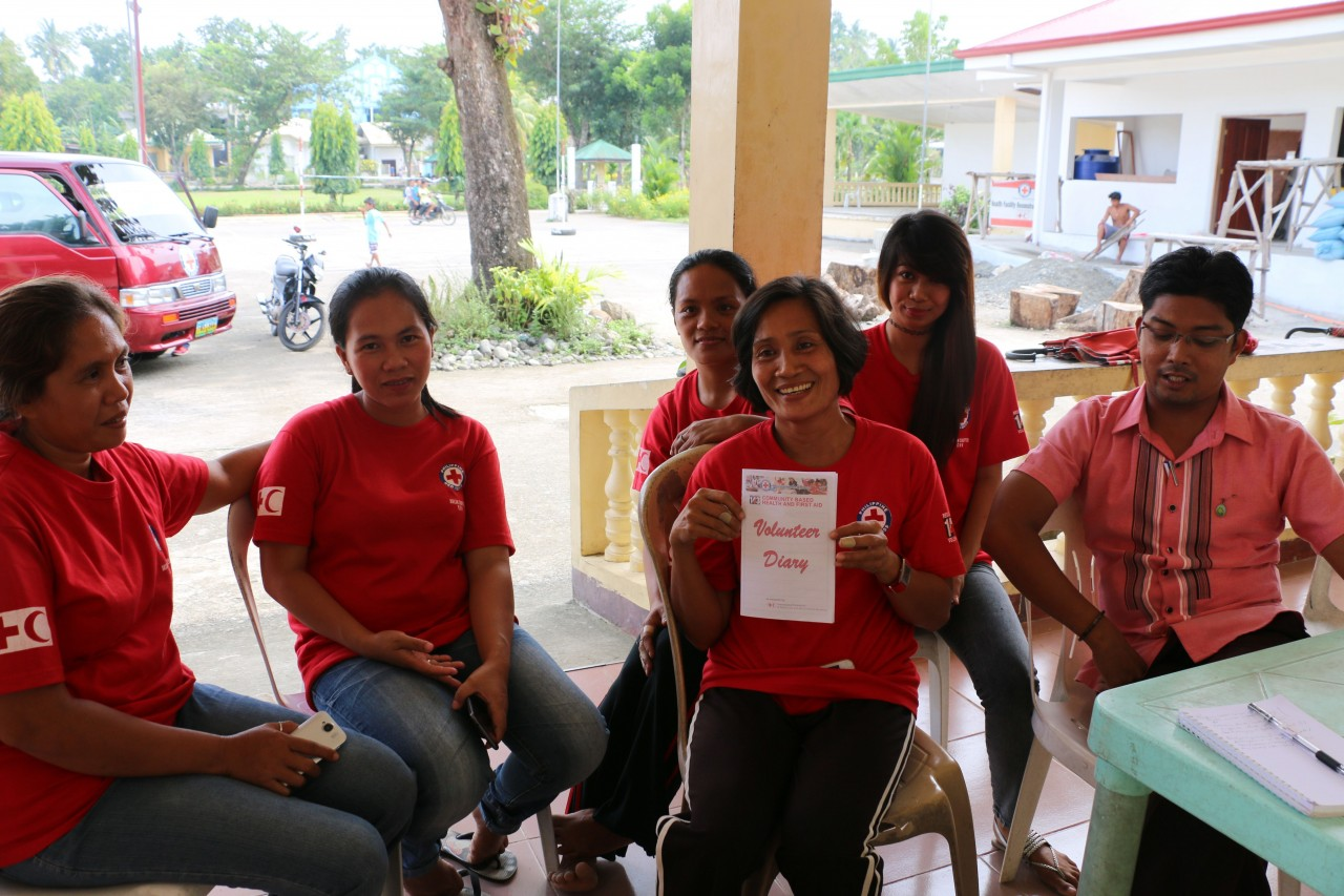 Philippines, Panay, Aklan, Malinao September 2015 Community Health volunteer Henriette (centre, with diary) did her training in September 2014 with the others in her group. She says being a Philippine Red Cross volunteer has changed her life and made her value her health and wellbeing. Now one of the main organisers of Barangay Rosario's popular zumba classes, Henriette shows her volunteer diary in which she records household visits, health sessions and clean up campaigns among other activities.