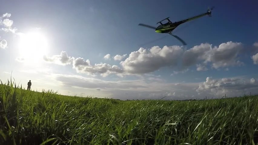 Large RC drone helicopter flying inverted upside down low above a green long grass field ...